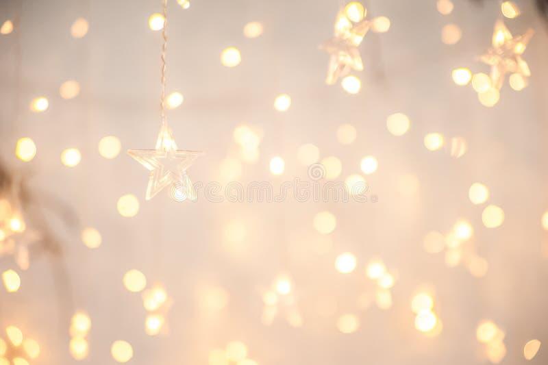 История гарлендов Нового года, как звезды Рождественская атмосфера с гарлендами в фокусе и дефокусировка стоковая фотография