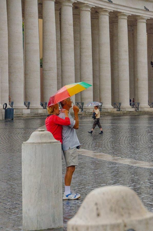 Италия Пары белого человека и женщины обняли под зонтиком в квадрате St Peter в Риме в июле 2013 стоковые изображения rf