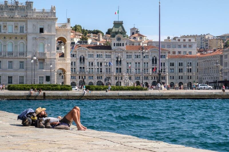 Италия, Триест, турист лежа в солнце на бесстрашной пристани стоковое фото