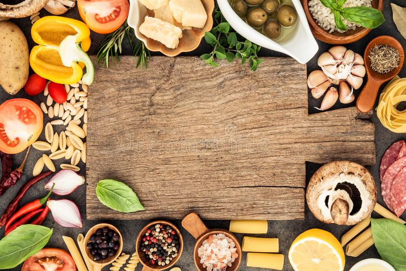 Итальянская еда варя ингридиенты на темной каменной предпосылке с c стоковые фотографии rf