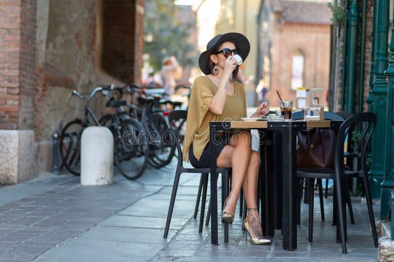 Итальянская женщина с шляпой и стеклами выпивает кофе стоковые изображения