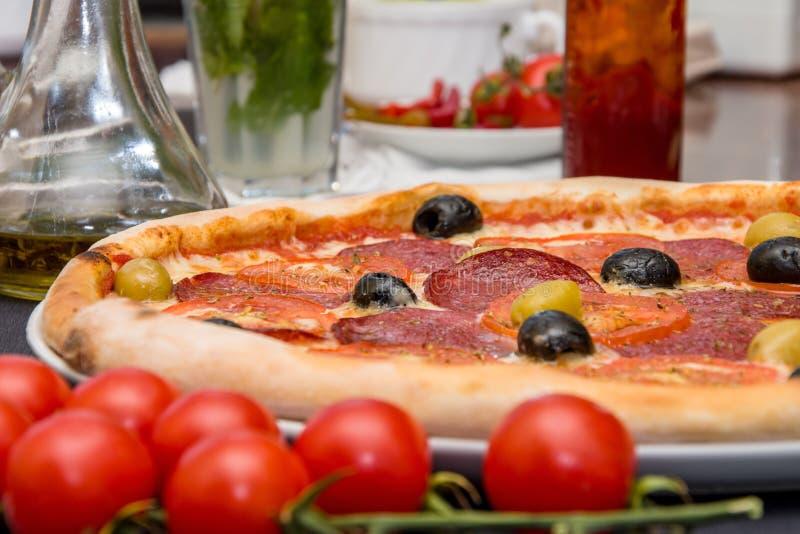 Итальянская пицца с сосиской и оливками на таблице около окна, еды в пиццерии стоковая фотография rf