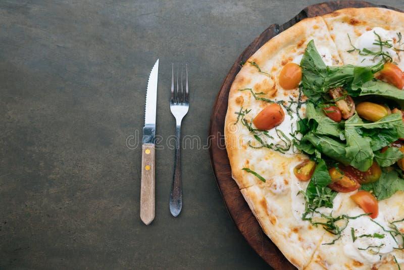 Итальянская пицца с сыром, томатами и базиликом burrata на черной каменной предпосылке с космосом экземпляра ножа и вилки r стоковое изображение