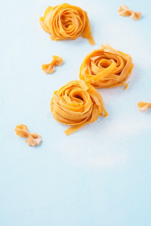 Итальянская предпосылка макаронных изделий Сырой fettuccine или tagliatelle стоковое изображение