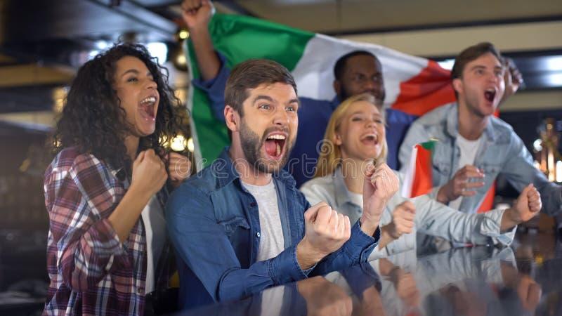 Итальянские вентиляторы с флагом празднуя выигрышное дело, наслаждаясь чемпионатом в баре стоковые фотографии rf