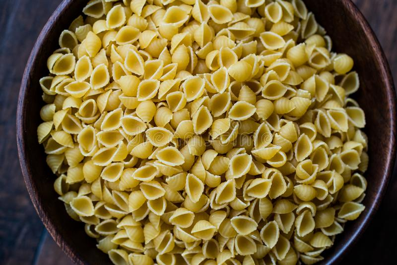 Итальянские каски Raw Pasta Shells Conchiglie / Conchiglioni в Wooden Bowl стоковое фото rf