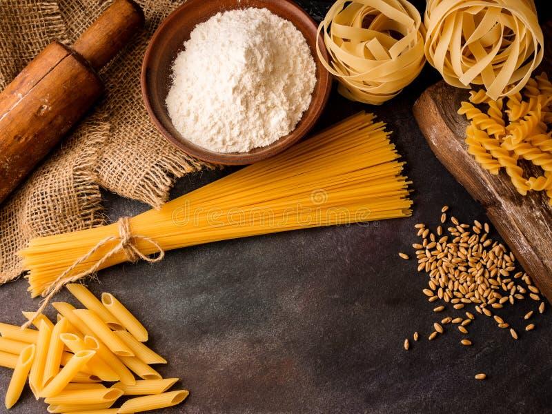 Итальянские макаронные изделия, спагетти, fettuccine, penne, вращающая ось, мука на текстурированной предпосылке r стоковое изображение