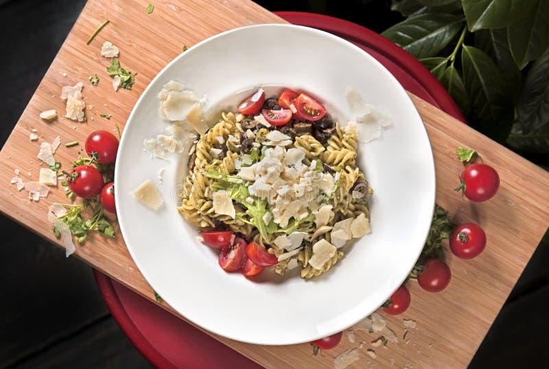 Итальянские макаронные изделия с томатами сыра пармезан и вишни стоковая фотография