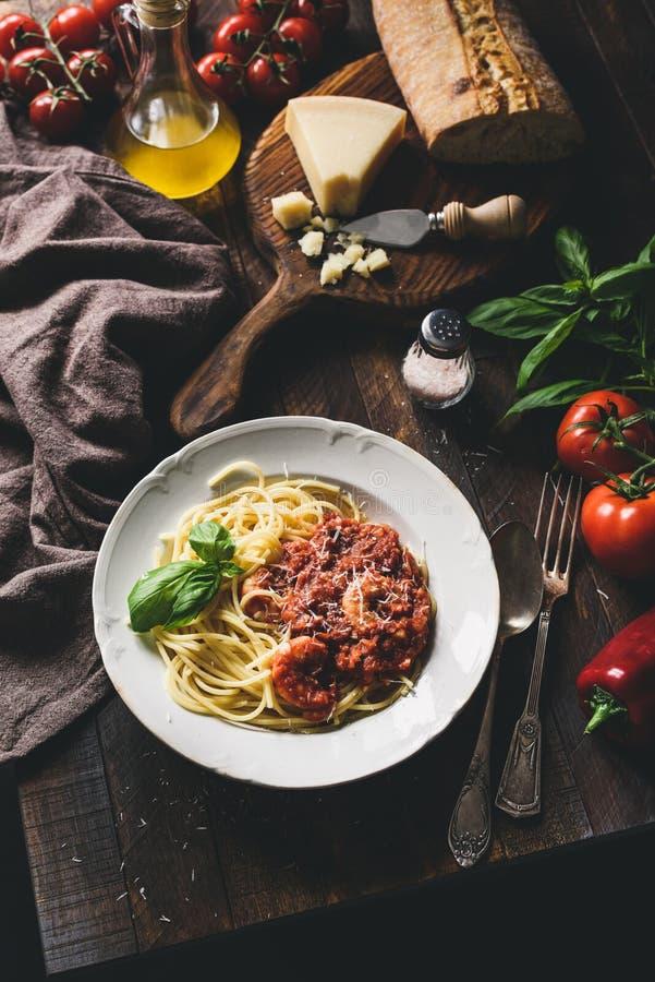 Итальянские макаронные изделия с томатным соусом, креветками и сыр пармесаном на деревенской деревянной таблице стоковое фото