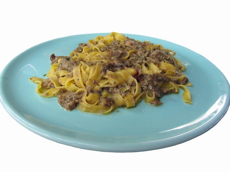 Итальянские свежие fettuccine или макаронные изделия tagliatelle с porcini величают на голубой плите изолированной на белой предп стоковое фото rf