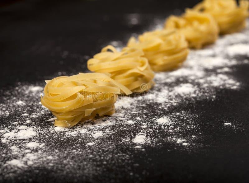 Итальянские традиционные сырцовые макаронные изделия на черной каменной предпосылке стоковое изображение