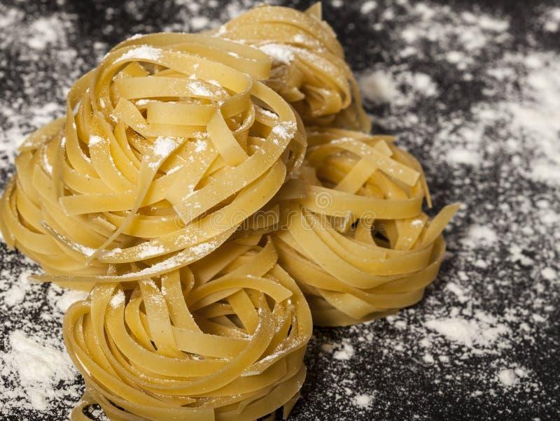 Итальянские традиционные сырцовые макаронные изделия на черной каменной предпосылке стоковые изображения