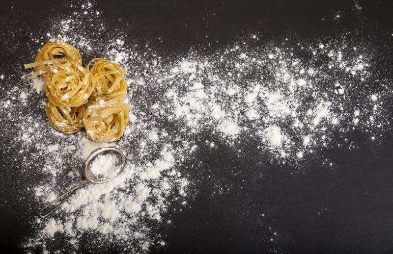 Итальянские традиционные сырцовые макаронные изделия на черной каменной предпосылке, взгляд сверху стоковое фото