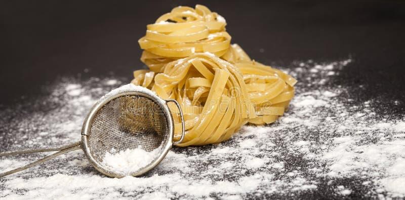 Итальянские традиционные сырцовые макаронные изделия на черной каменной предпосылке стоковые фото