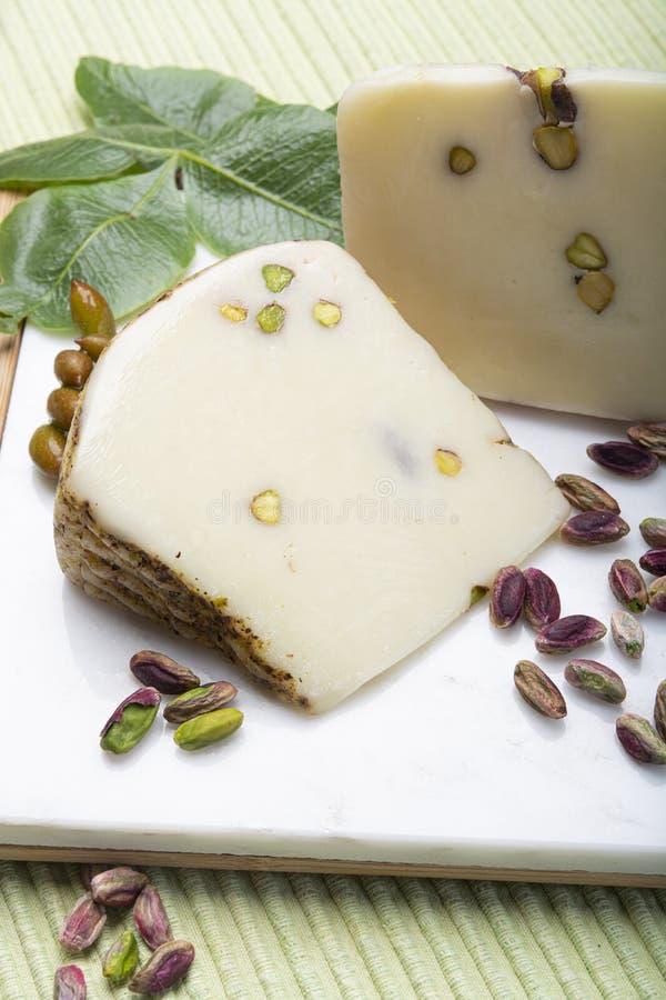 Итальянские provolone или сыр provola сделанный в Сицилии с вкусными зелеными гайками фисташки Bronte служили на белом мраморном  стоковые изображения rf