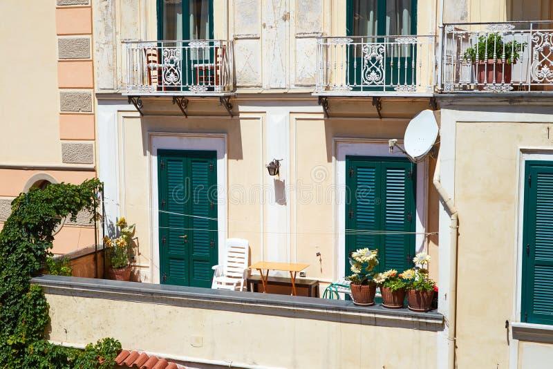 Итальянский балкон с цветками и закрытыми зелеными штарками стоковая фотография rf