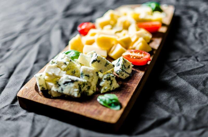 Итальянский диск деликатеса antipasti сыра против черной предпосылки стоковое изображение rf