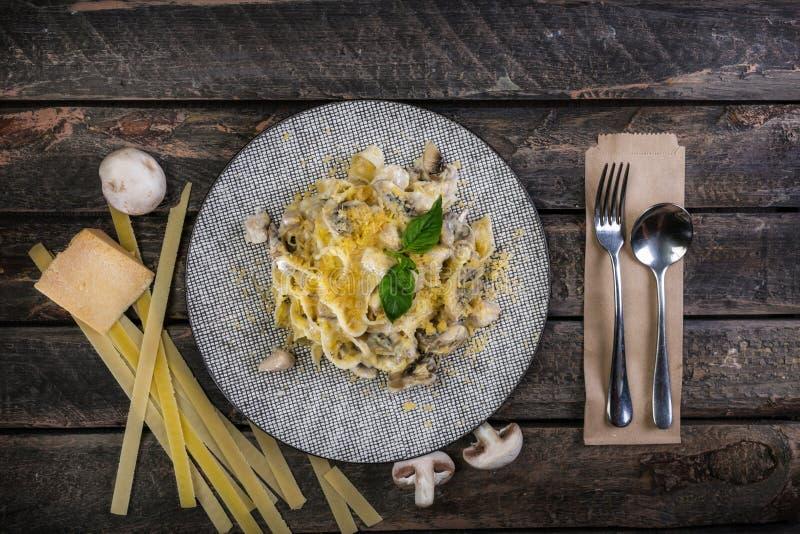 Итальянский fettuccine макаронных изделий с сыром, цыпленком и грибами, служил на красивой керамической плите со столовым приборо стоковое фото