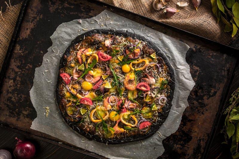 Итальянская пицца с черными тестом и морепродуктами на подносе выпечки от печи стоковая фотография