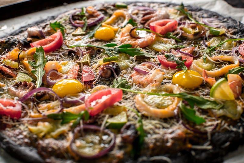 Итальянская пицца с черными тестом и морепродуктами на подносе выпечки от печи стоковое изображение