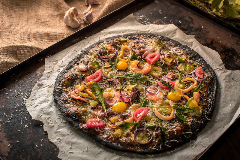 Итальянская пицца с черными тестом и морепродуктами на подносе выпечки от печи стоковая фотография rf