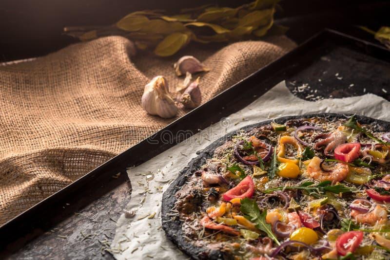 Итальянская пицца с черными тестом и морепродуктами на подносе выпечки от печи стоковые изображения rf