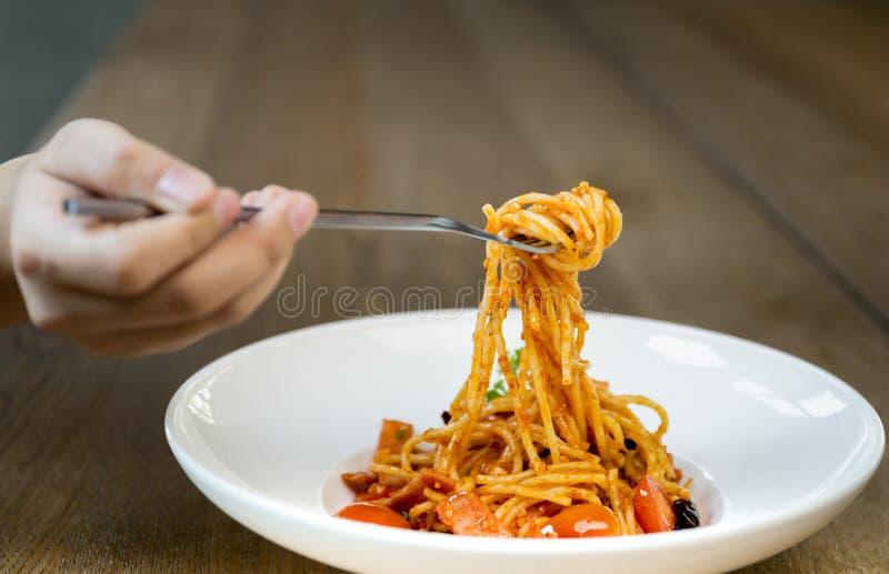 Итальянская рука еды держа вилку с спагетти bolognese в белизне стоковые фотографии rf