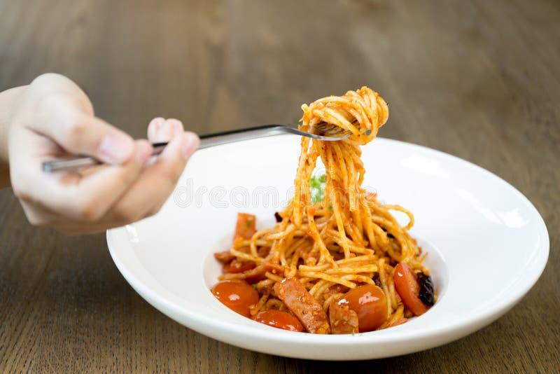 Итальянская рука еды держа вилку с спагетти bolognese в белизне стоковые изображения