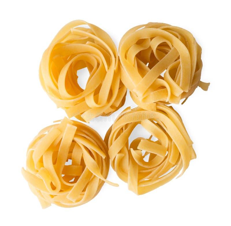 Итальянские гнезда fettuccine или макаронных изделий tagliatelle изолированные на белой предпосылке стоковые фото