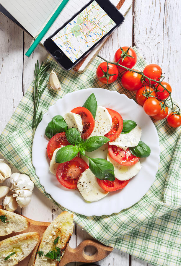 Итальянский традиционный салат Caprese с картой t smartphone путешественника стоковая фотография rf