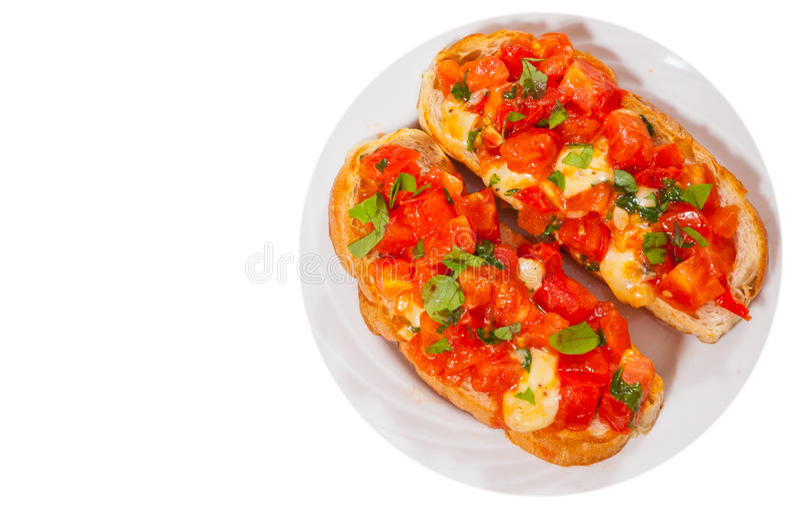 Итальянское bruschetta томата с прерванными овощами, травами, сыром и маслом на зажаренном или провозглашанном тост покрытом корк стоковая фотография