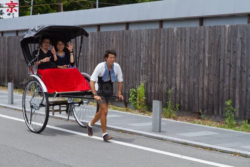 Июнь 2012 - Arashiyama, Япония: Азиатский человек вытягивая вытягиванную рикшу с развевать 2 людей сидя на камере стоковое фото rf
