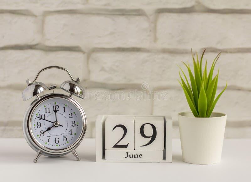 29 июня на деревянном календаре рядом с будильником на столе Летний день, пустое место для текста Дата календаря, день рождения и стоковое изображение