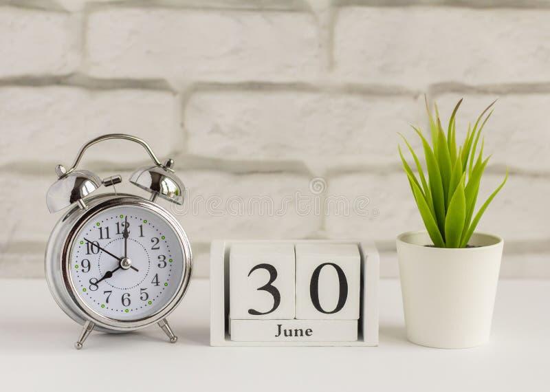 30 июня на деревянном календаре рядом с будильником на столе Летний день, пустое место для текста Дата календаря, день рождения и стоковая фотография