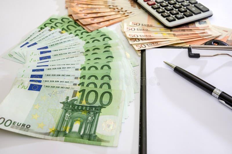 100 и 50 евро, калькулятор, ручка на белой предпосылке стоковое фото