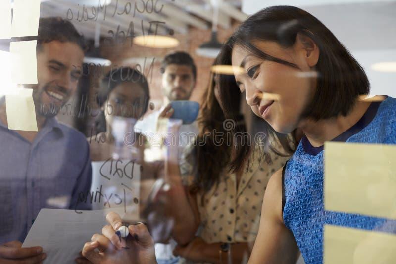 Идеи сочинительства коммерсантки на стеклянном экране во время встречи стоковое фото rf