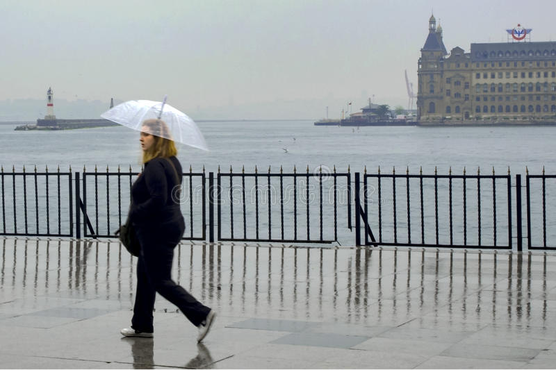 Идите дождь в Стамбуле, людях пробуйте достигнуть пристань парома в k стоковые фотографии rf