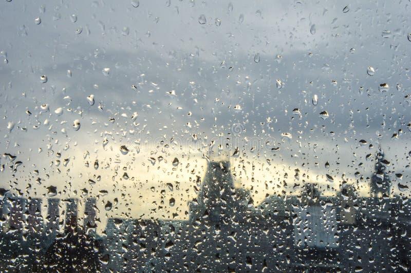 Идите дождь на окне в городской местности с расстоянием из фокуса с Лондоном стоковое фото rf
