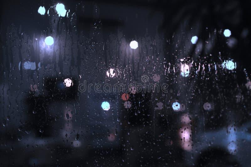 Идите дождь падения на окне с светами bokeh улицы стоковое фото rf