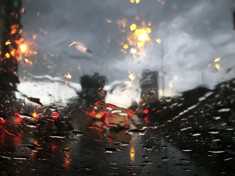 Идите дождь падения на стекле фронта автомобиля и плохом движении стоковые изображения rf