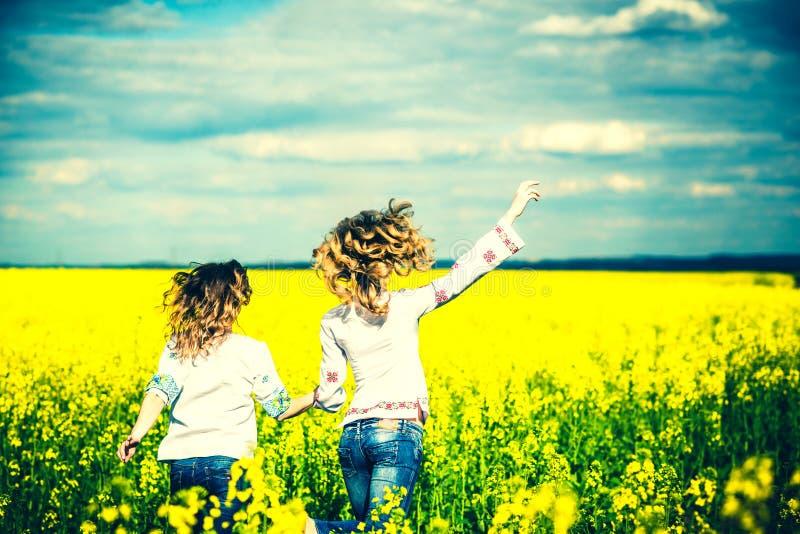 Идти милых девушек внешний в поле в рубашках вышивки стоковые изображения