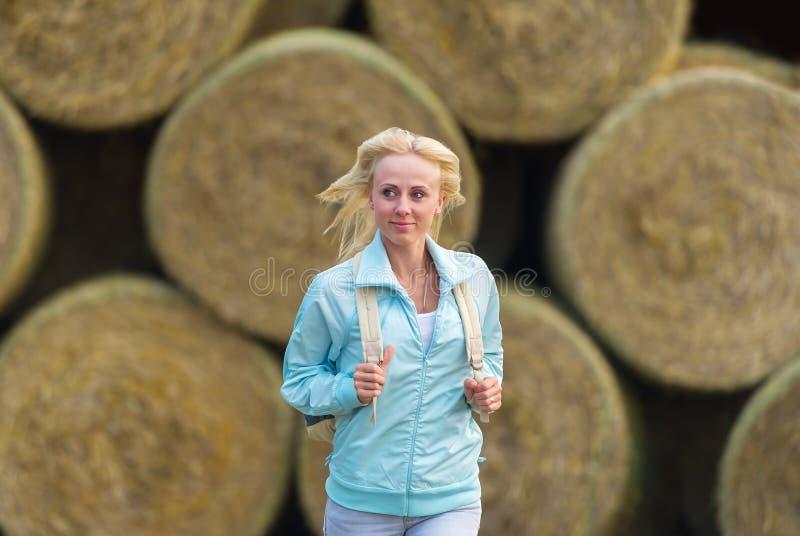 Идущая романтичная девушка outdoors против стога сена стоковое изображение