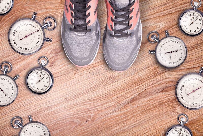 Идущее оборудование Секундомер и идущие ботинки женщин Время для бега Аксессуары спорта идущие на деревянном поле стоковая фотография rf