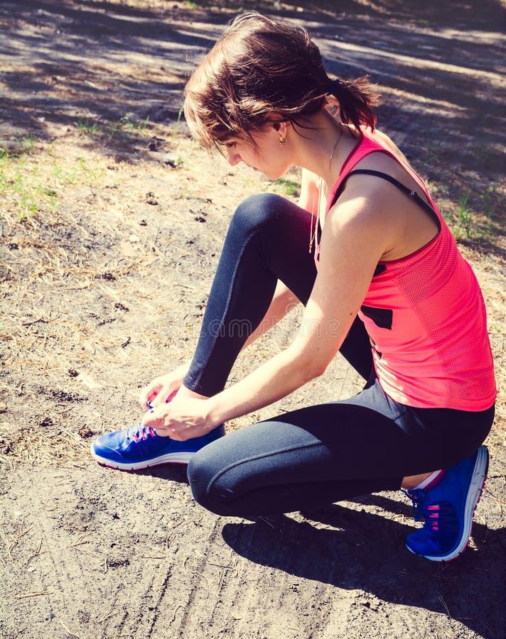 Идущие ботинки Крупный план женщины связывая шнурки ботинка Женский спорт f стоковое изображение