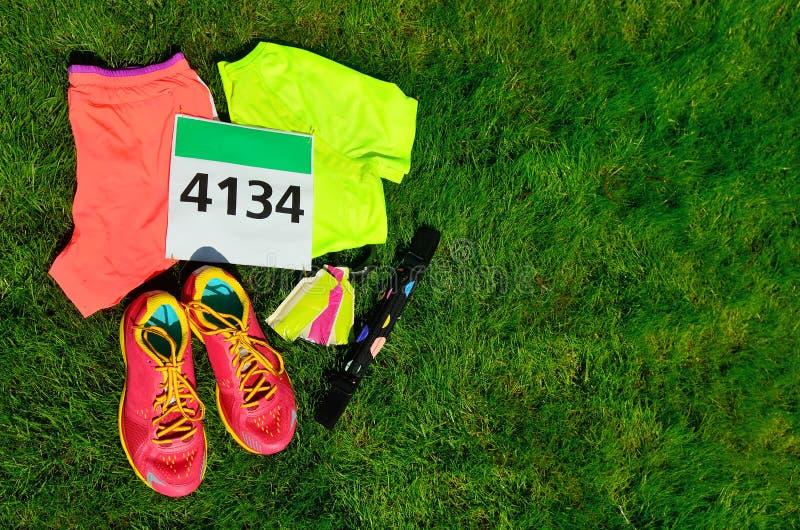 Идущие ботинки, номер bib гонки марафона, бегуны зацепляют и гели энергии на предпосылке травы, спорте, фитнесе стоковая фотография rf