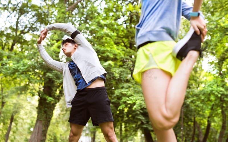 Идущие пары протягивая и нагревая в парке перед тренировкой стоковые изображения rf