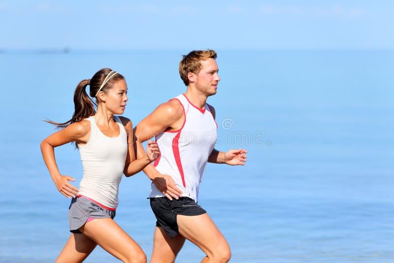Идущие пары jogging на пляже стоковые изображения rf
