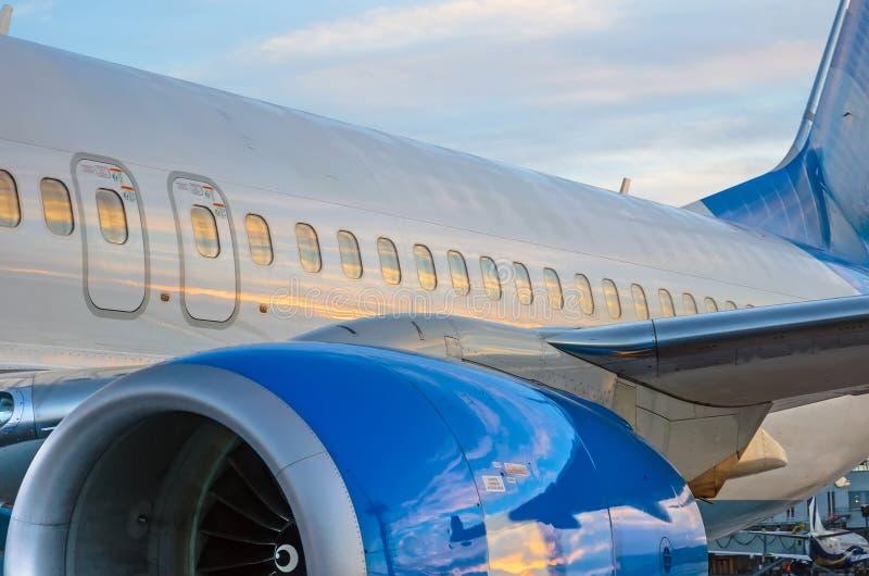 Иллюминаторы самолета, двигатель, кабель На заходе солнца на авиапорте стоковые изображения