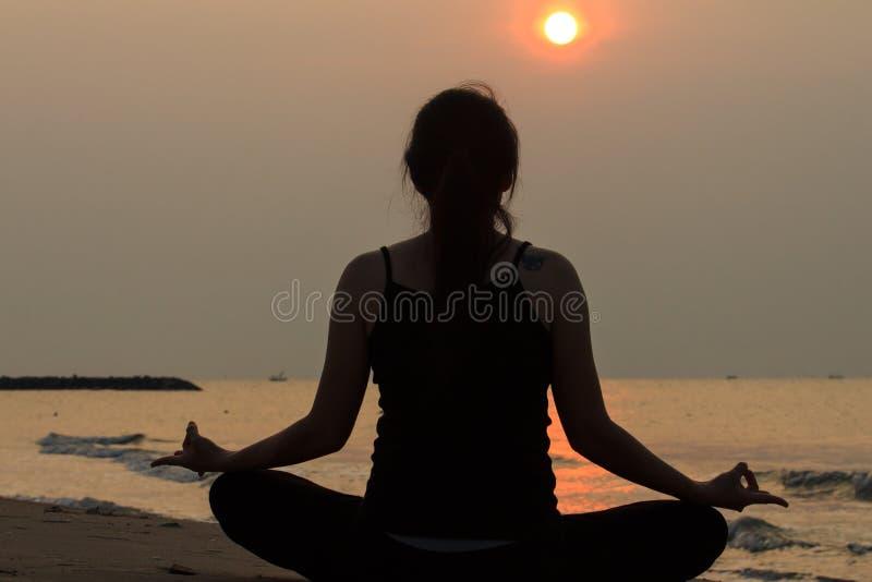 Йога азиатской женщины практикуя на море мира в утре стоковые изображения