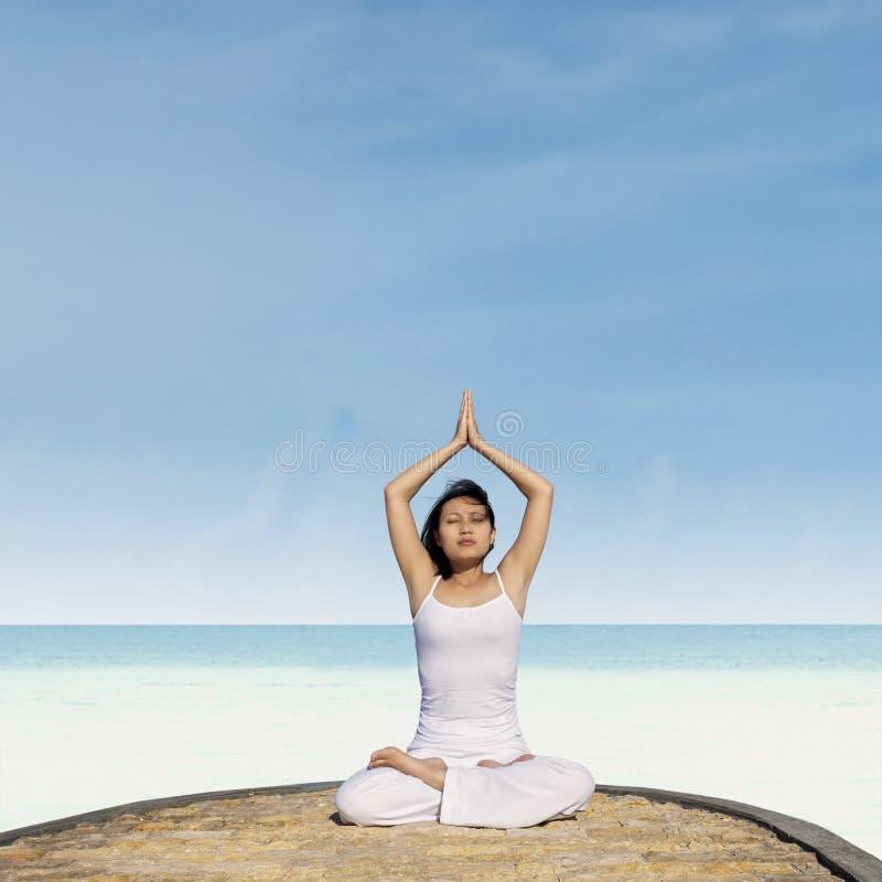 Йога азиатской женщины практикуя на пляже стоковые фото